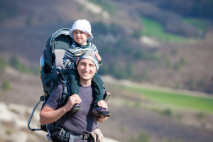 Father is hiking with the 1.5 year baby in baby carrier