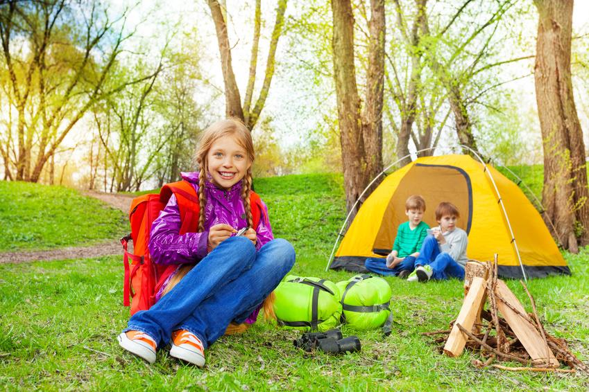 Happy children relax near the wooden bonfire, tent