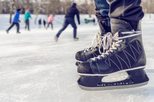 Close-up of ice skating shoes on a rink, with people skating in the background (Lafontaine Park, Montreal, Canada)